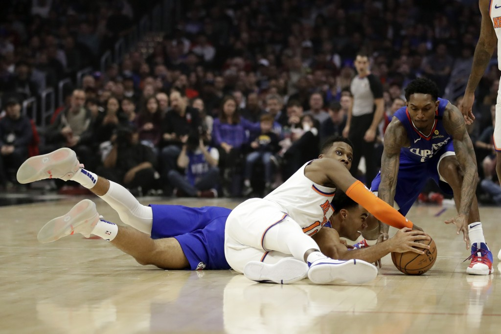 New York Knicks' Frank Ntilikina, front center, works for the ball against Los Angeles Clippers' Jerome Robinson, back center, and Lou Williams during...