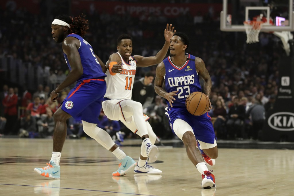 Los Angeles Clippers' Lou Williams, right, dribbles around a screen set by teammate Montrezl Harrell, left, on New York Knicks' Frank Ntilikina (11) d...