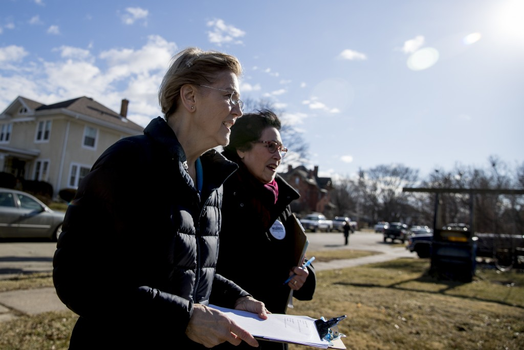 Democratic presidential candidate Sen. Elizabeth Warren, D-Mass., left, accompanied by Jackson County Democratic Party chair Donna Duvall, right, knoc...