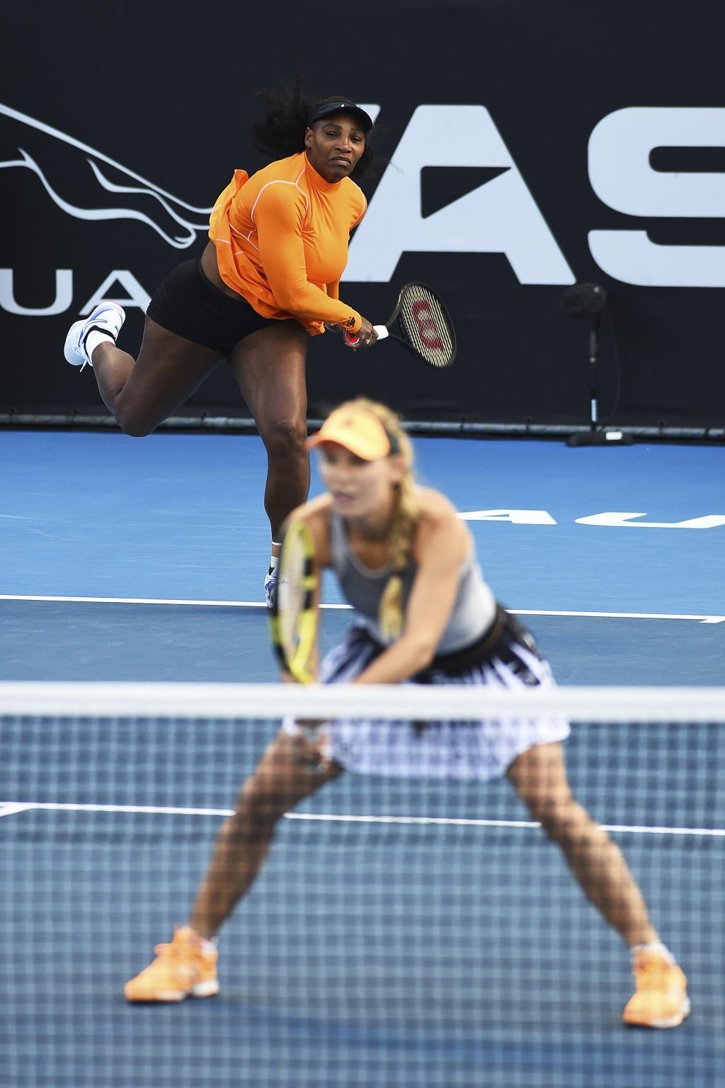 Untied States' Serena Williams, rear, serves as Denmark's Caroline Wozniacki looks on during their first round doubles match against Japan's Nao Hibin...