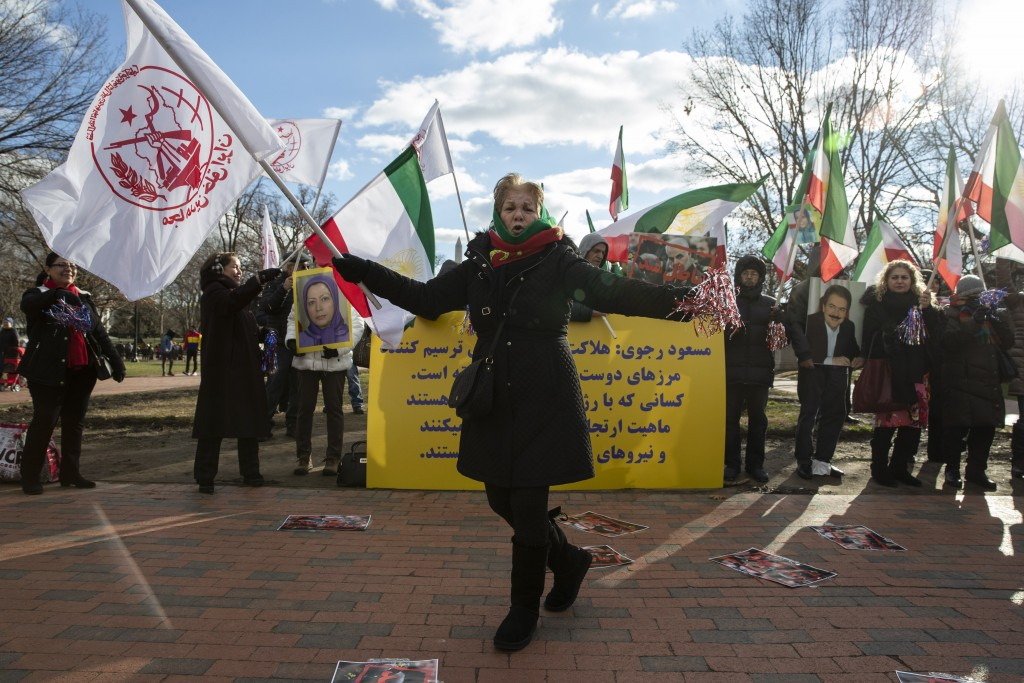 A supporters of the Mujahedeen-e-Khalq, or the MEK, an Iranian exile group, dances as others hold signs and flags during a show of support for a U.S. ...