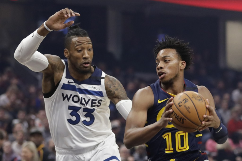 Cleveland Cavaliers' Darius Garland (10) drives past Minnesota Timberwolves' Robert Covington (33) in the first half of an NBA basketball game, Sunday...