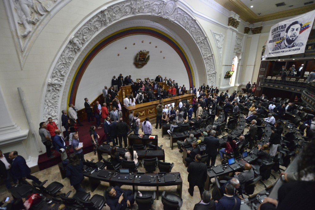 Lawmakers move about the chamber as they swear-in lawmaker Luis Parra as National Assembly president after many opposition lawmakers, including opposi...