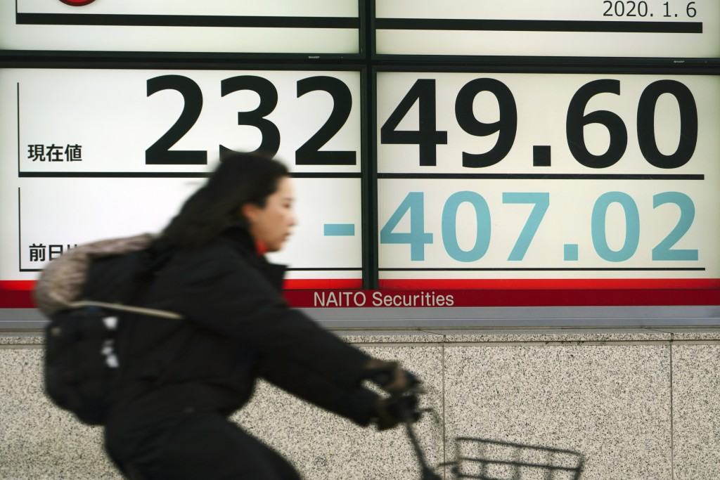 A woman rides a bicycle past at an electronic stock board showing Japan's Nikkei 225 index at a securities firm in Tokyo Monday, Jan. 6, 2020, in Toky...