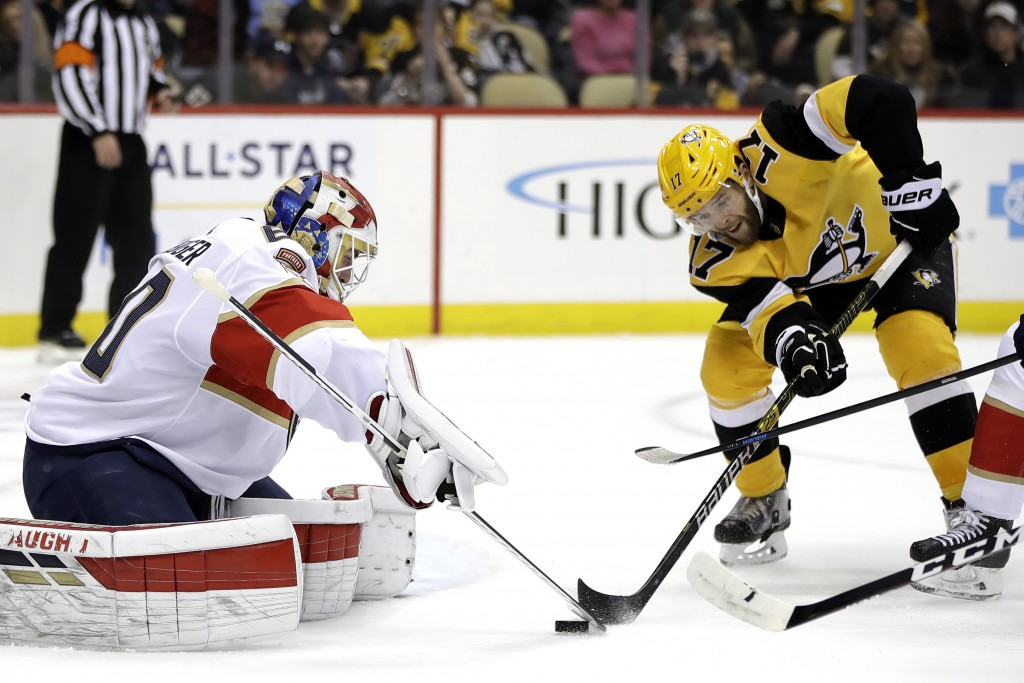 Pittsburgh Penguins' Bryan Rust (17) cannot get his stick on a rebound in front of Florida Panthers goaltender Chris Driedger (60) during the second p...