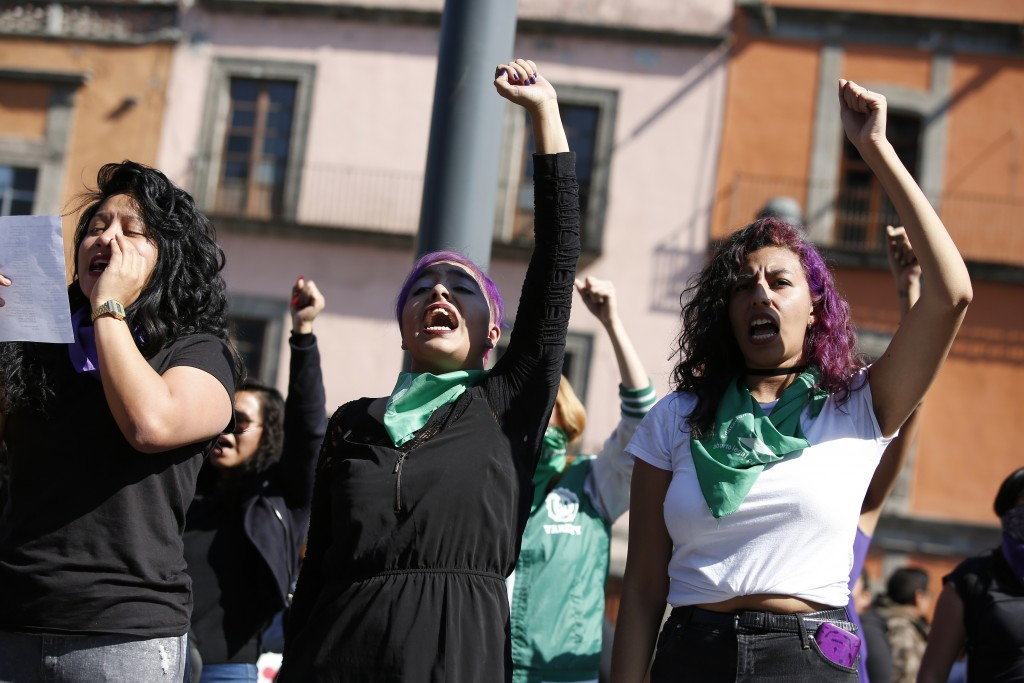 Perla Rosales, 26, center, and Marian Lira, 24, right, participate in a performance in support of abortion rights next to the cathedral in Mexico City...