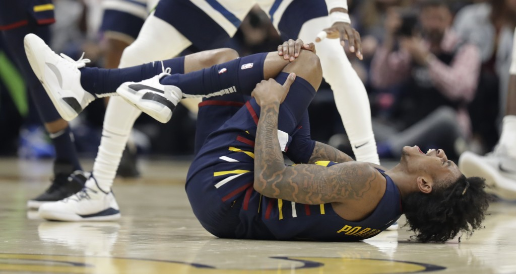 Cleveland Cavaliers' Kevin Porter Jr. holds his knee after an injury in the second half of an NBA basketball game against the Minnesota Timberwolves, ...
