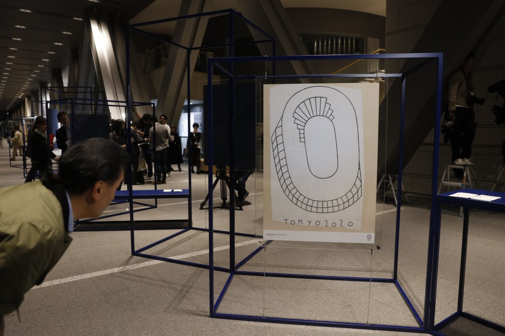 A journalist looks at a poster created by Philippe Weisbecker, one of 20 posters officially selected for the Tokyo Olympics and Paralympics, at the Mu...