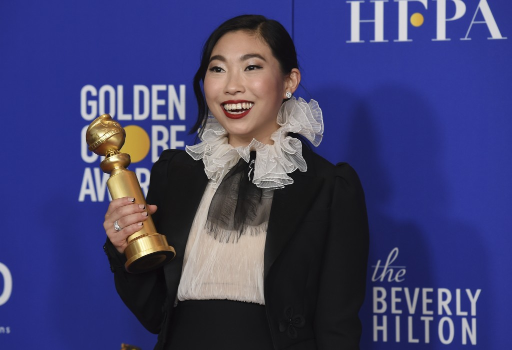"""Awkwafina poses in the press room with the award for best performance by an actress in a motion picture, musical or comedy for """"The Farewell"""" at the 7..."""