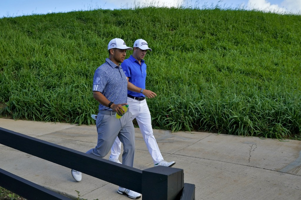 Xander Schauffele, left, and Justin Thomas walk down the cart path on the 12th fairway during final round of the Tournament of Champions golf event, S...