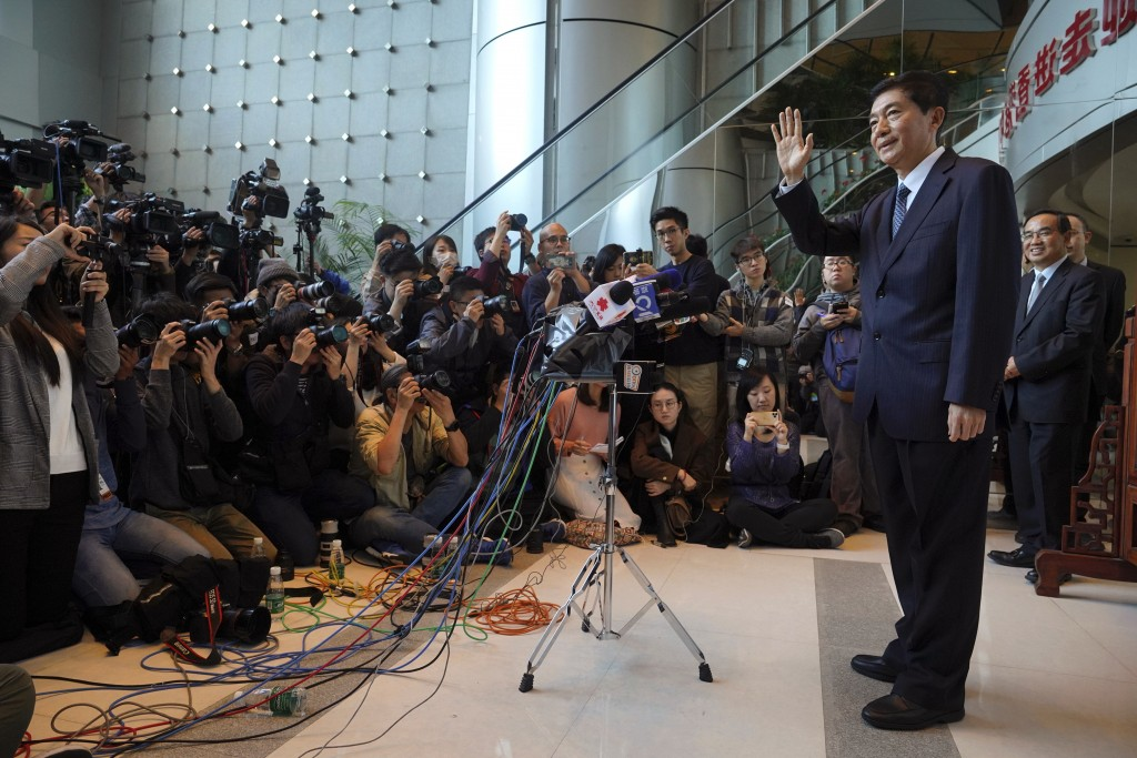 Newly appointed head of China's liaison office in Hong Kong, Luo Huining, right, waves as he arrives for a media briefing at the China's liaison offic...
