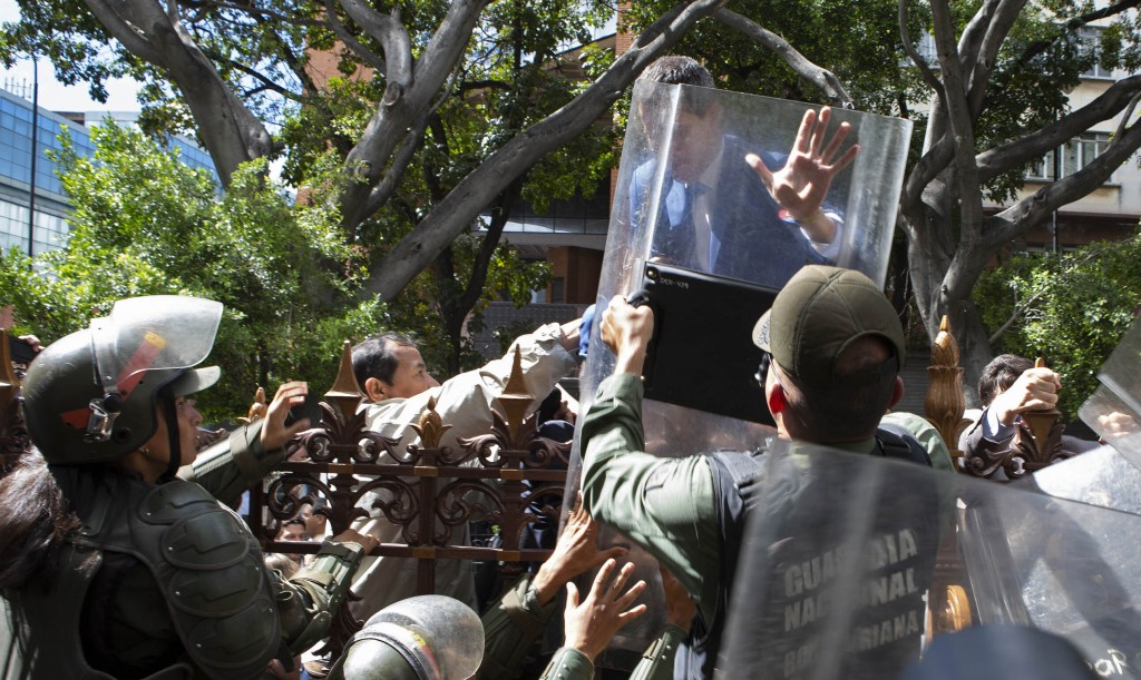 National Assembly President Juan Guaido, Venezuela's opposition leader, tries to climb the fence past National Guards to enter the compound of the Ass...