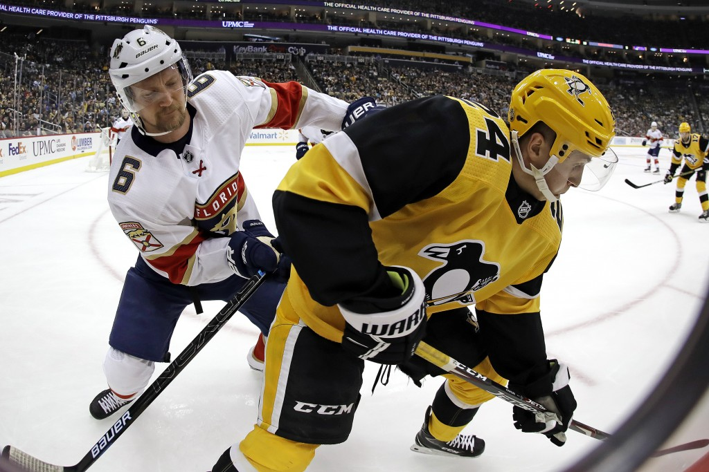 Pittsburgh Penguins' Dominik Kahun, right, is checked in the corner by Florida Panthers' Anton Stralman (6) during the second period of an NHL hockey ...