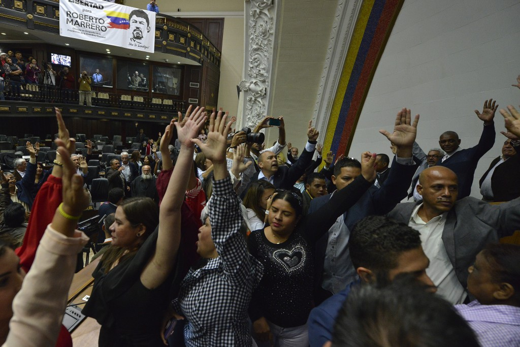Lawmakers raise their hands to vote in lawmaker Luis Parra as president of the National Assembly, while many opposition lawmakers, including Assembly ...