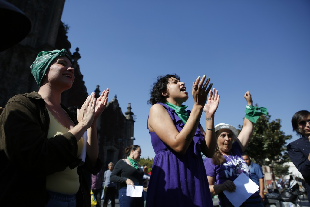Priscila Alvarado, 25, left, with other women shout out after a performance in support of abortion-rights next to the cathedral in Mexico City, Sunday...