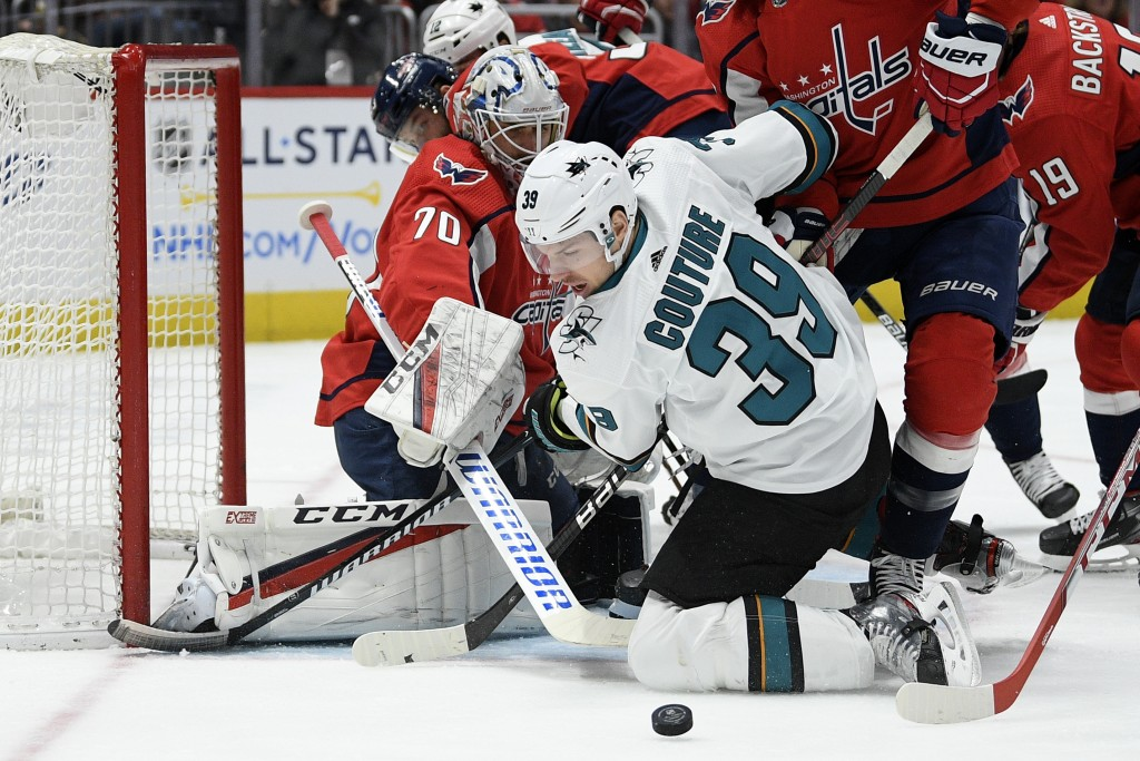 Washington Capitals goaltender Braden Holtby (70) and San Jose Sharks center Logan Couture (39) battle for the puck during the first period of an NHL ...