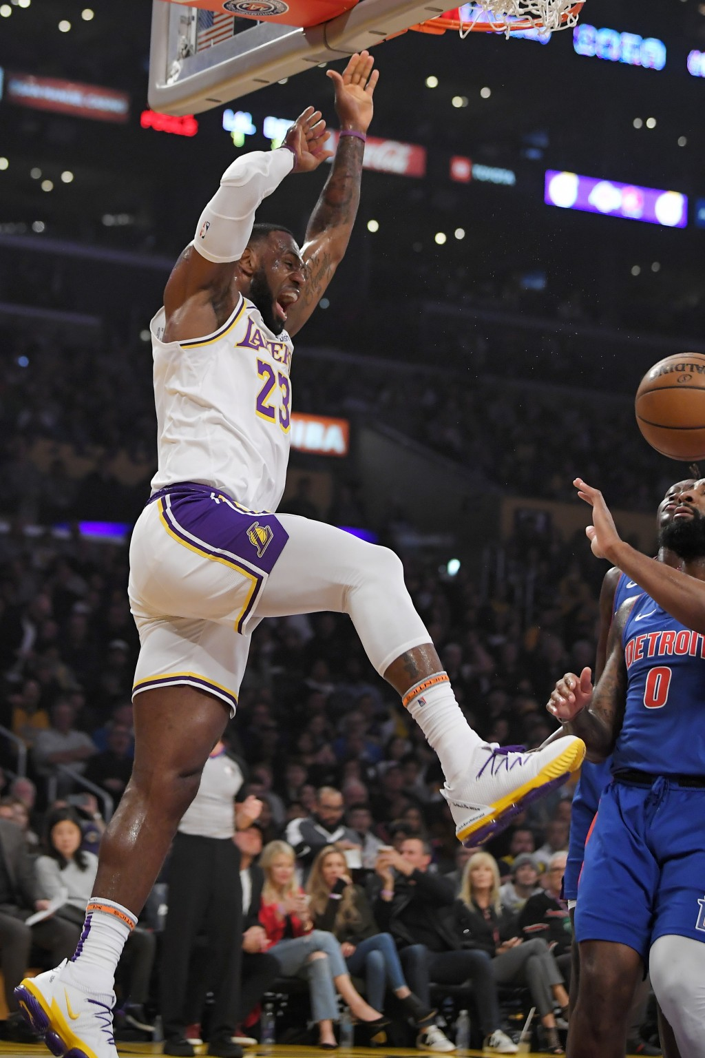 Los Angeles Lakers forward LeBron James, left, dunks as Detroit Pistons center Andre Drummond watches during the first half of an NBA basketball game ...