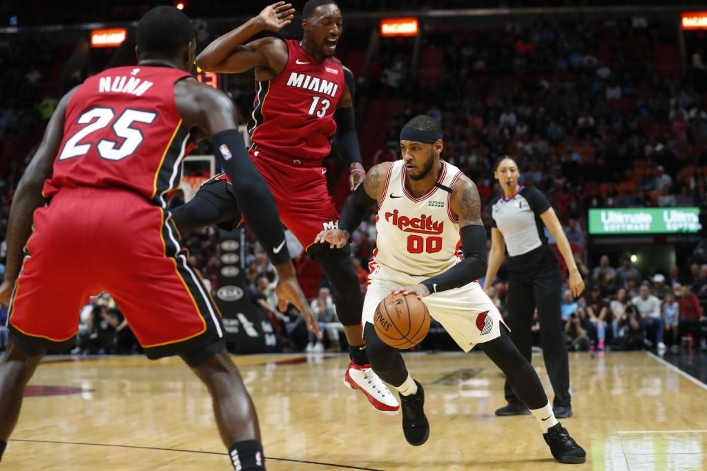 Portland Trail Blazers forward Carmelo Anthony (00) drives to the basket against Miami Heat guard Kendrick Nunn (25) and center Bam Adebayo (13) durin...