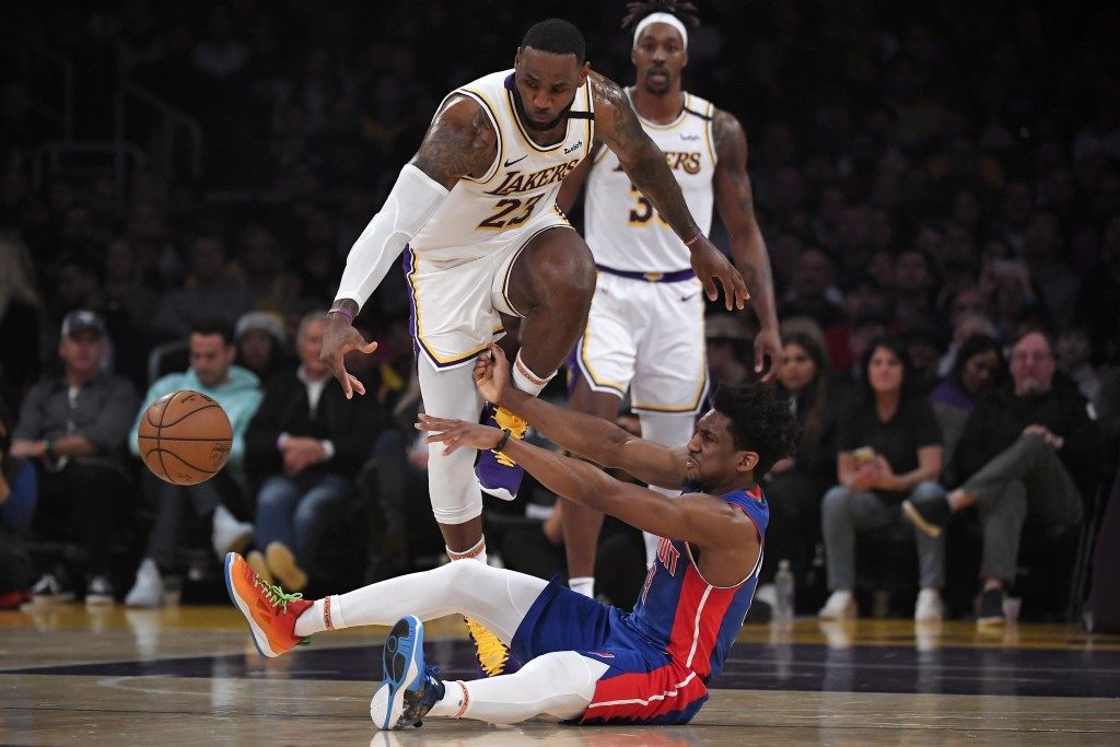 Detroit Pistons guard Langston Galloway, below, passes the ball from the floor as Los Angeles Lakers forward LeBron James, upper left, reaches for it ...