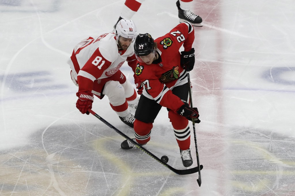Detroit Red Wings center Frans Nielsen, left, and Chicago Blackhawks defenseman Adam Boqvist battle for the puck during the first period of an NHL hoc...