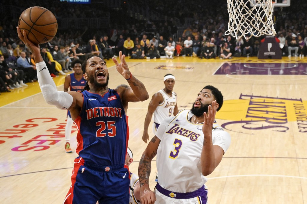 Detroit Pistons guard Derrick Rose, left, shoots as Los Angeles Lakers forward Anthony Davis defends during the first half of an NBA basketball game S...
