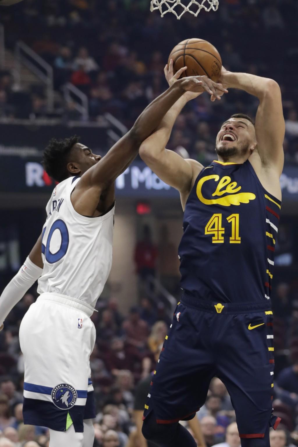 Minnesota Timberwolves' Kelan Martin, left, fouls Cleveland Cavaliers' Ante Zizic in the first half of an NBA basketball game, Sunday, Jan. 5, 2020, i...
