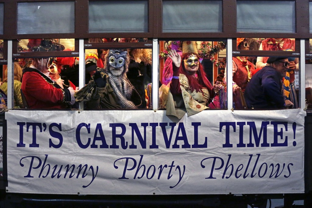 FILE - This Jan. 6, 2015, file photo, shows members of the Phunny Phorty Phellows, celebrating aboard a streetcar in New Orleans. It's the official en...