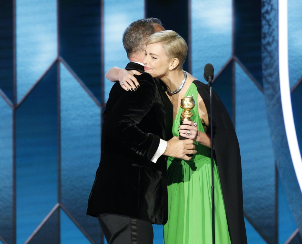 This image released by NBC shows Tom Hanks accepting the Cecil B. DeMille Award from presenter Charlize Theron at the 77th Annual Golden Globe Awards ...