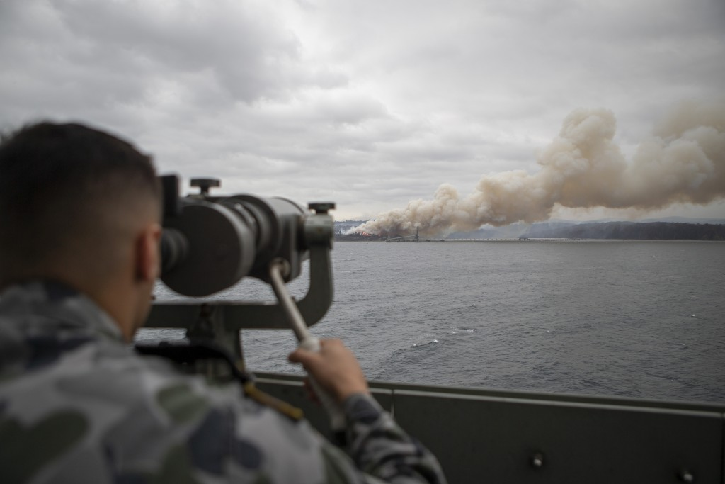 In this photo provided by the Australian Department of Defence on Jan. 6, 2020, Seaman Boatswains Mate Malik El-Leissy watches a burning fire from HMA...