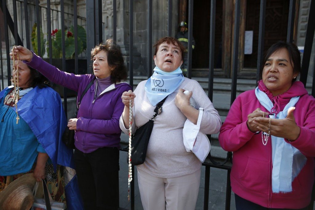 Women pray against abortion during a performance in support of abortion rights next to the cathedral in Mexico City, Sunday, Jan. 5, 2020. Mexico's ru...