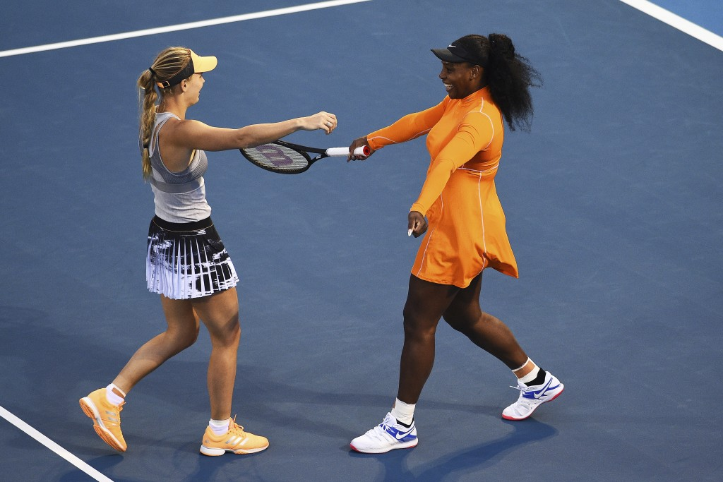 Denmark's Caroline Wozniacki, left, and Untied States' Serena Williams, right, celebrate their win during their first round doubles match against Japa...