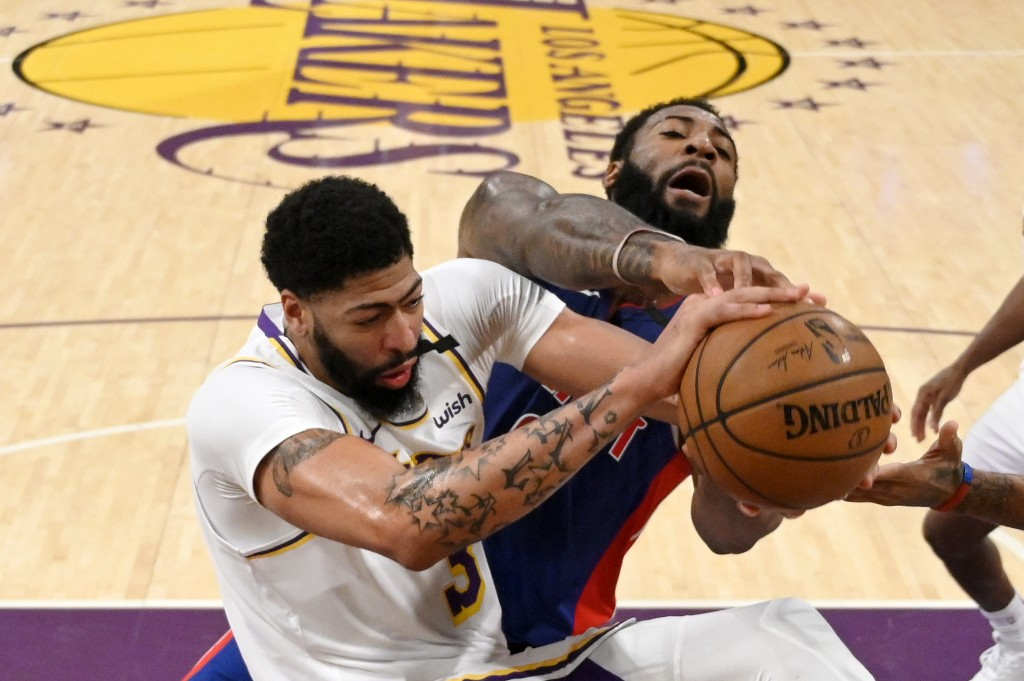 Los Angeles Lakers forward Anthony Davis, left, and Detroit Pistons center Andre Drummond grapple for the ball during the first half of an NBA basketb...