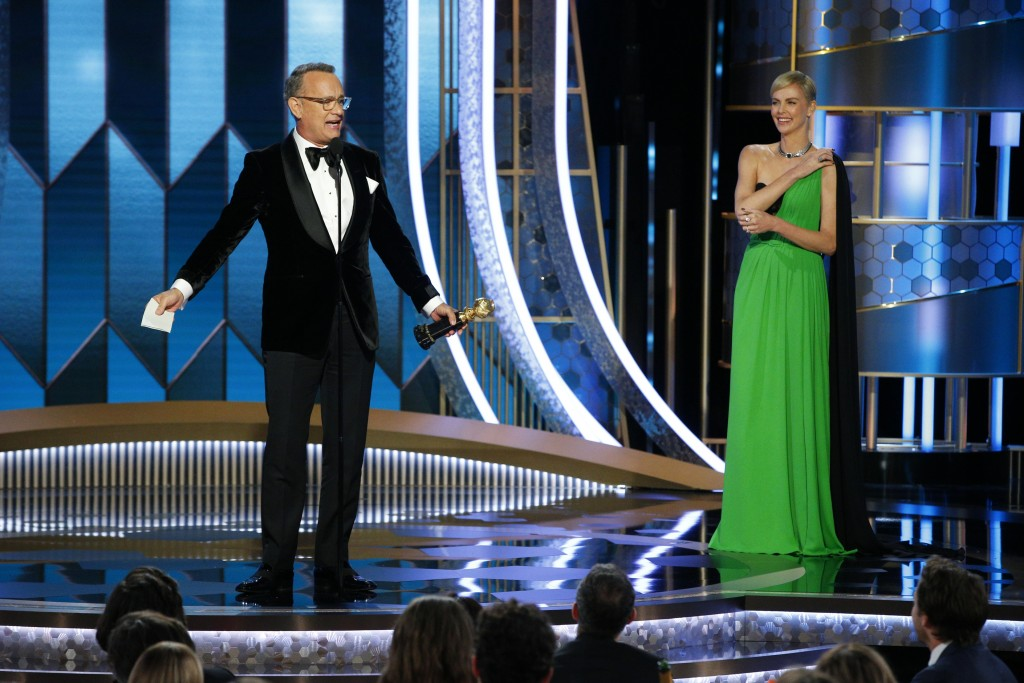 This image released by NBC shows Tom Hanks accepting the Cecil B. DeMille Award as presenter Charlize Theron looks on at right at the 77th Annual Gold...