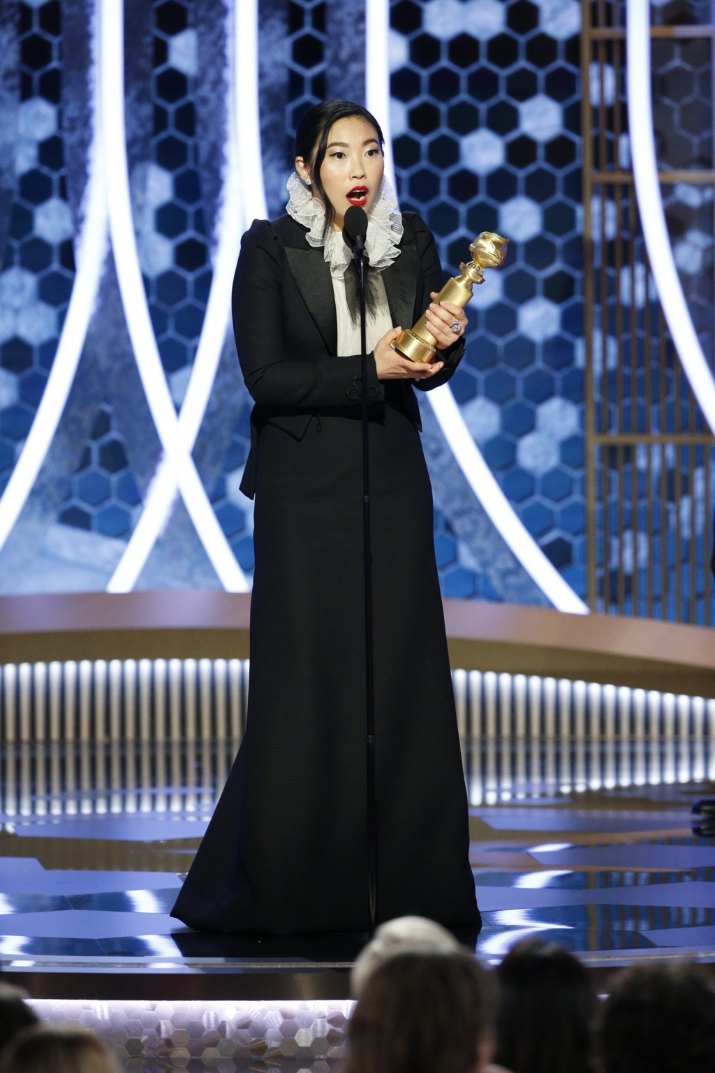 """This image released by NBC shows Awkwafina accepting the award for best actress in a motion picture comedy for her role in """"The Farewell"""" at the 77th ..."""