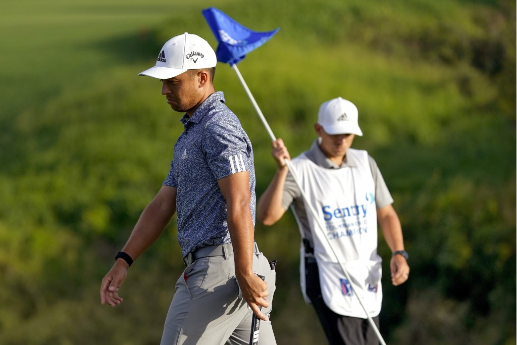 Xander Schauffele looks towards his ball after missing his putt to lose on the first of three playoff holes on the 18th green during final round of th...