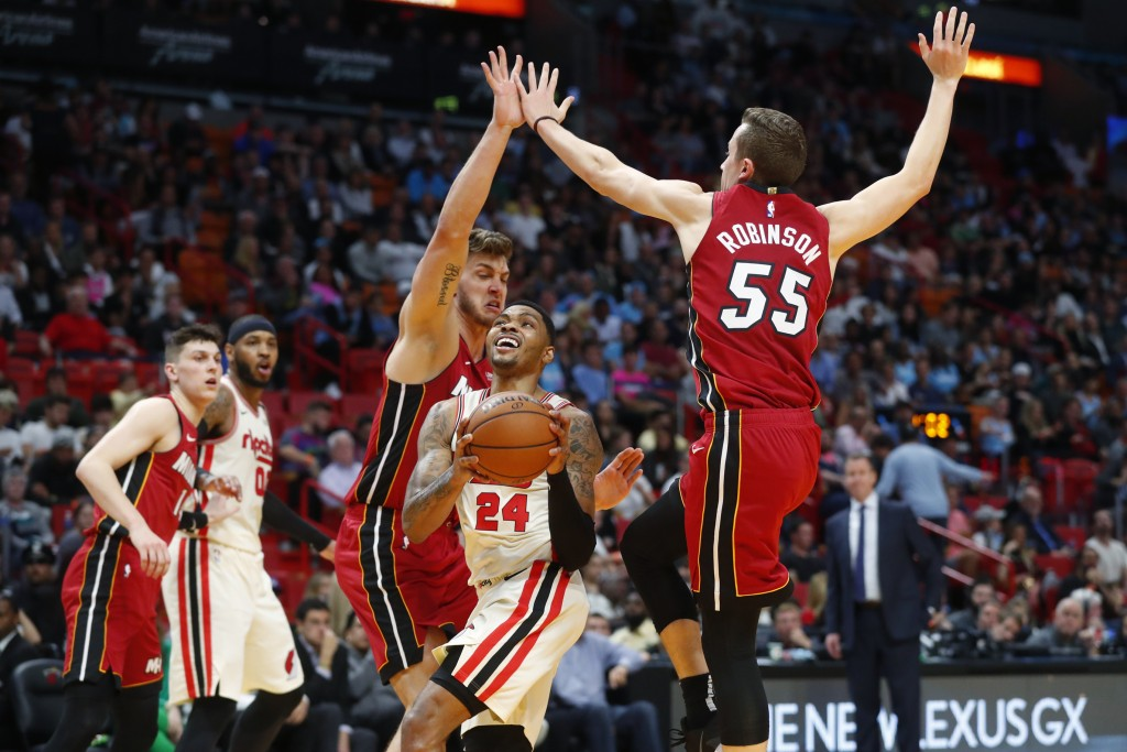 Portland Trail Blazers guard Kent Bazemore (24) goes up to shoot against Miami Heat forwards Duncan Robinson (55) and Meyers Leonard during the first ...