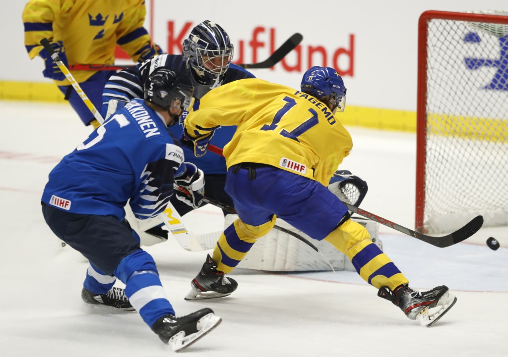 Finland's Mikko Kokkonen, left, and Finland's Justus Annunen, center, fail to stop Sweden's Samuel Fagemo, right, from scoring his sides second goal d...