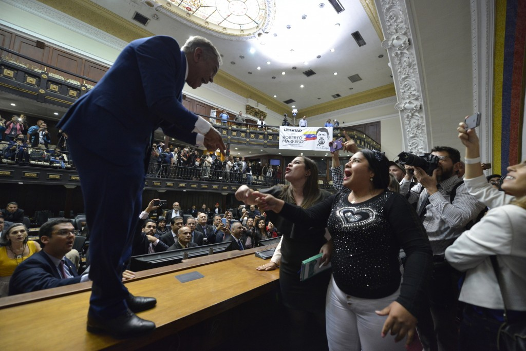 Opposition lawmaker William Barrientos stands on a desk to argue with ruling party lawmakers after many of his allies, including Assembly President Ju...