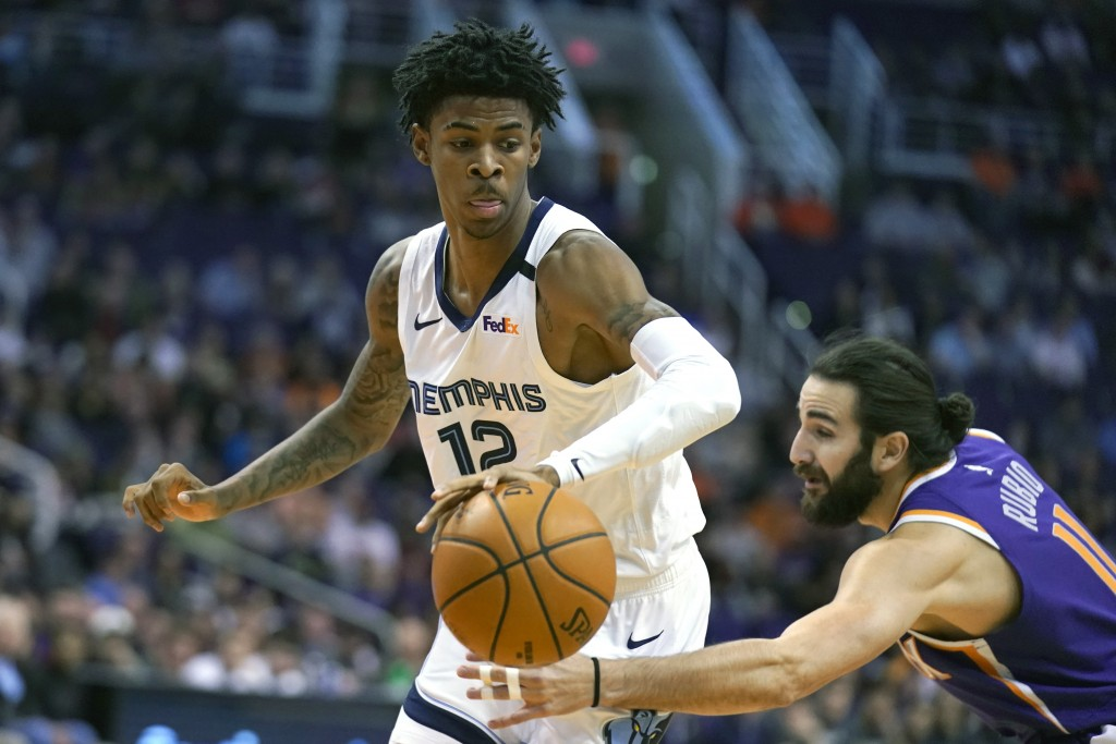 Memphis Grizzlies guard Ja Morant (12) drives against Phoenix Suns guard Ricky Rubio in the first half during an NBA basketball game, Sunday, Jan. 5, ...