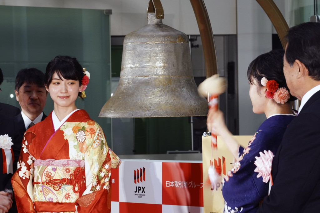 A kimono-clad employee of the Tokyo Stock Exchange tolls a bell during a ceremony marking the start of this year's trading in Tokyo Monday, Jan. 6, 20...