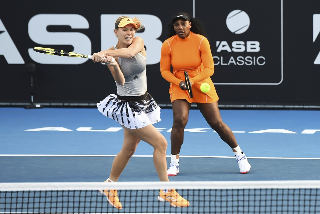 Denmark's Caroline Wozniacki plays a backhand as Untied States' Serena Williams looks on during their first round doubles match against Japan's Nao Hi...