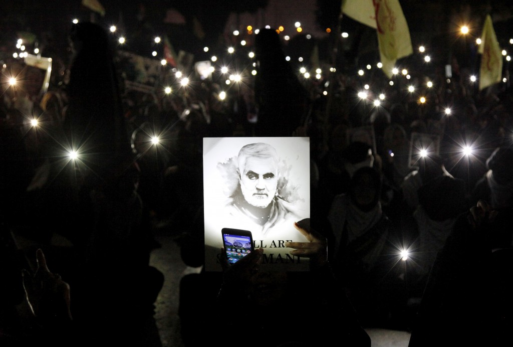 A Shiite Muslim illuminates a portrait of Iranian Revolutionary Guard Gen. Qassem Soleimani, with light from a mobile phone, during a rally to condemn...