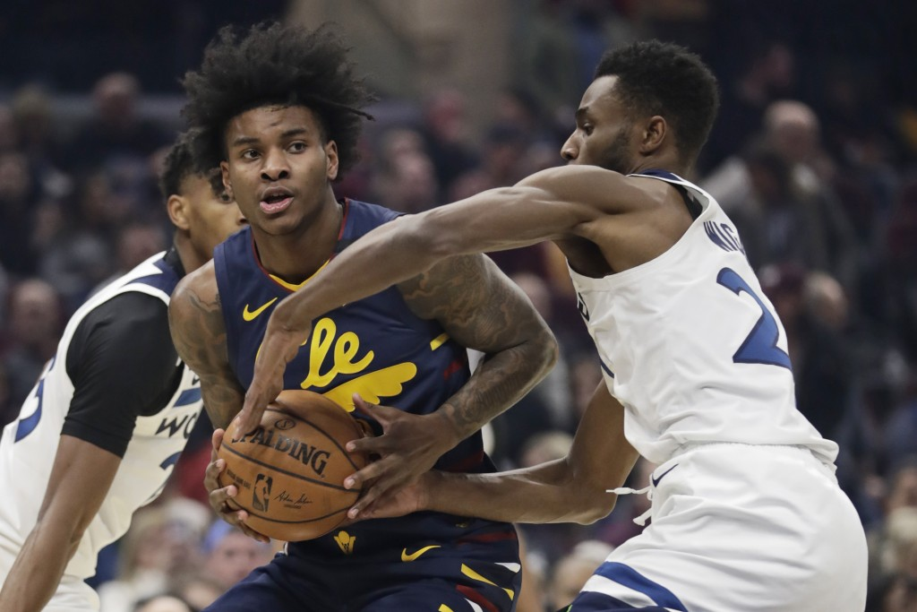 Cleveland Cavaliers' Kevin Porter Jr., left, drives past Minnesota Timberwolves' Andrew Wiggins in the first half of an NBA basketball game, Sunday, J...