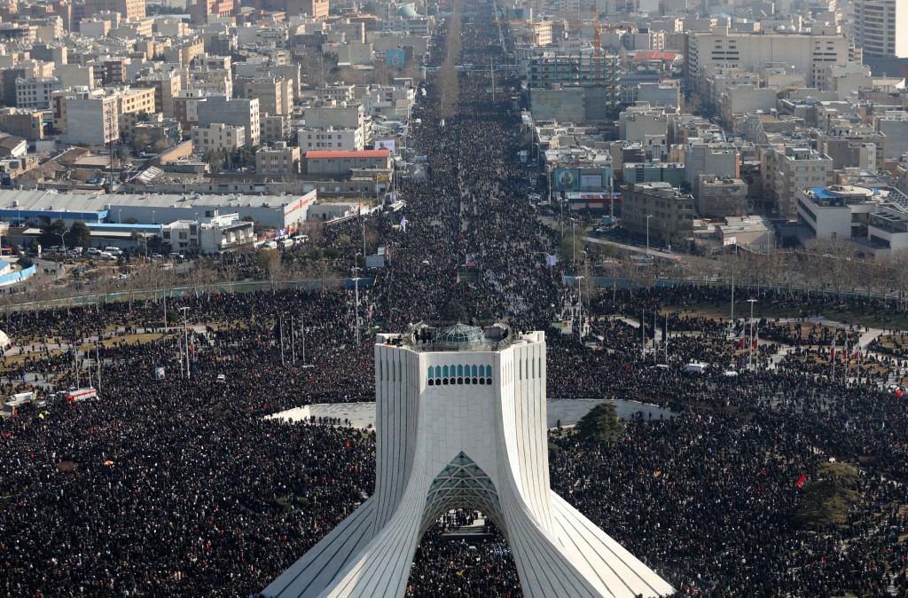 In this photo released by the official website of the Office of the Iranian Supreme Leader, mourners attend a funeral ceremony for Iranian Gen. Qassem...