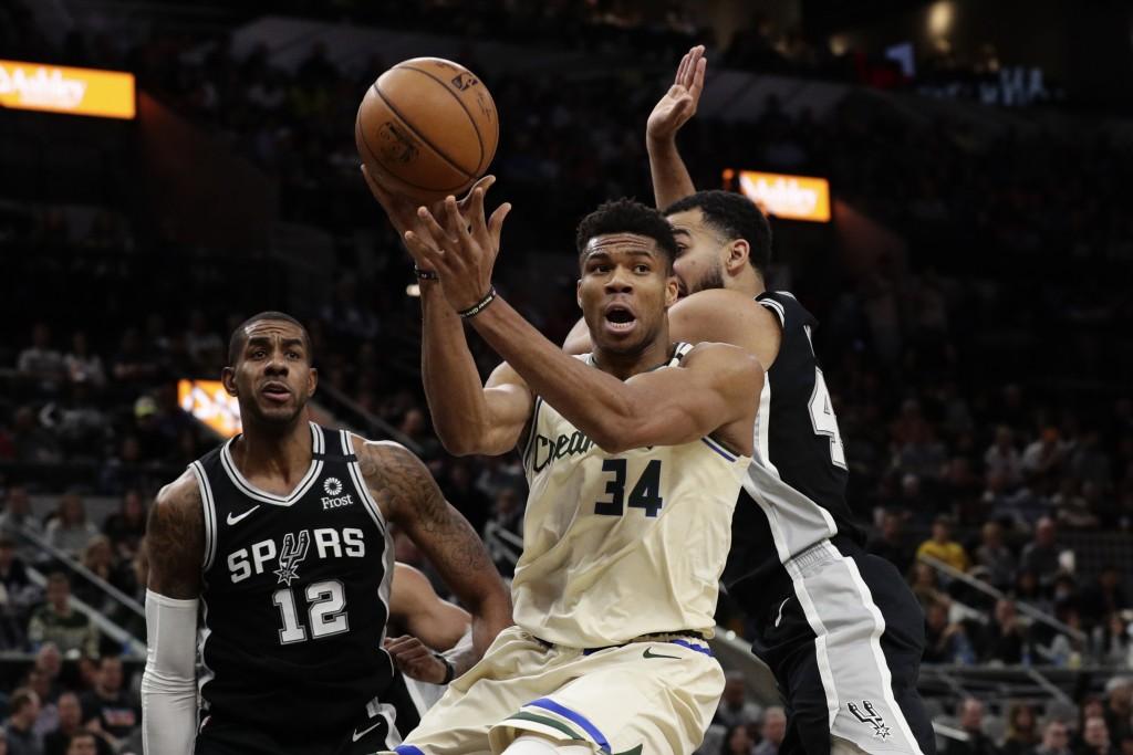 Milwaukee Bucks forward Giannis Antetokounmpo (34) passes the ball as San Antonio Spurs center LaMarcus Aldridge (12) watches during the first half of...