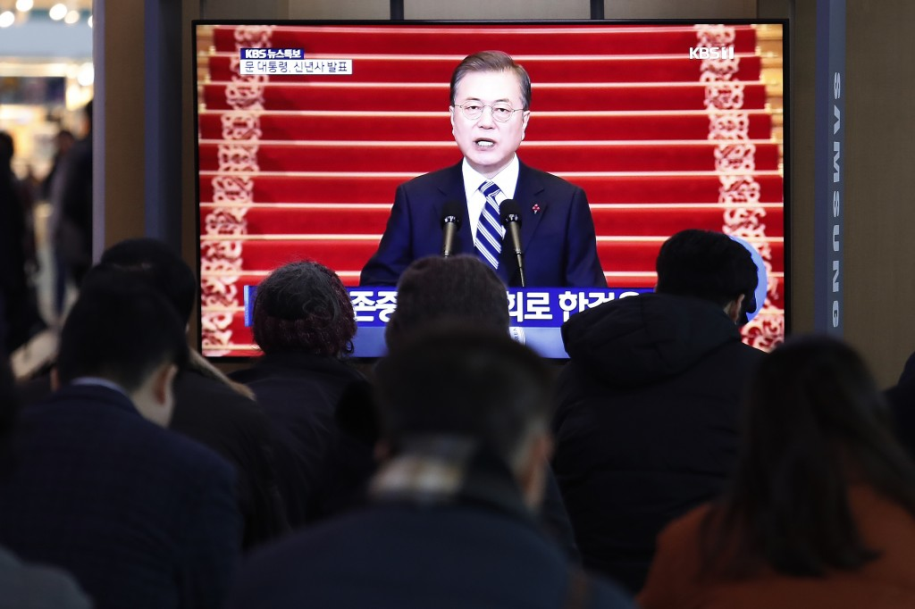 People watch a TV screen showing the live broadcast of South Korean President Moon Jae-in's New Year's speech at the Seoul Railway Station in Seoul, S...
