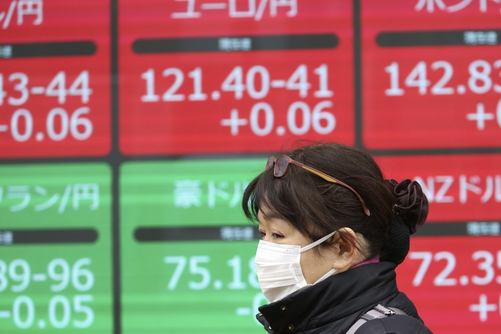 A woman walks by an electronic stock board of a securities firm in Tokyo, Tuesday, Jan. 7, 2020. Shares are climbing in Asia following modest gains on...