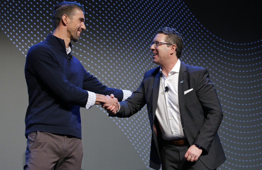 Michael Moskowitz, CEO of Panasonic Corporation of North America, right, shakes hand with Michael Phelps during a Panasonic news conference before the...