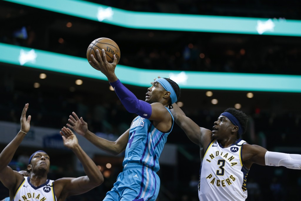 Charlotte Hornets guard Devonte' Graham, center, drives to the basket between Indiana Pacers center Myles Turner, left, and guard Aaron Holiday in the...