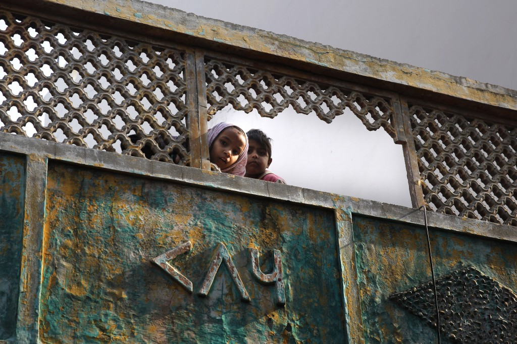 In this Tuesday, Dec. 24, 2019, photo, Muslim children look through broken fencing of their balcony in a congested neighborhood where five people died...